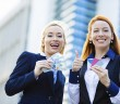 Happy business women holding credit cards and cash reward
