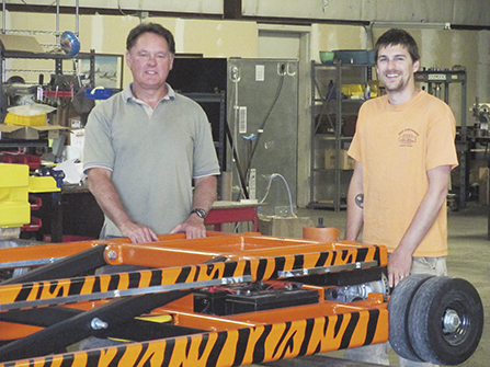 Steve Hill and Andrew Waltosz, standing next to a Tiger Tug. Photo by Gregg Morris