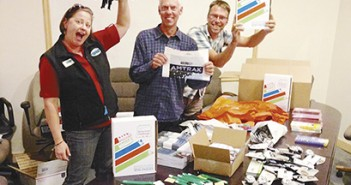 Kim Curley, Jeff Monson and Brian Potwin prepare prizes and giveaways for the 2014 Drive Less Challenge. Photo provided by Commute Options.