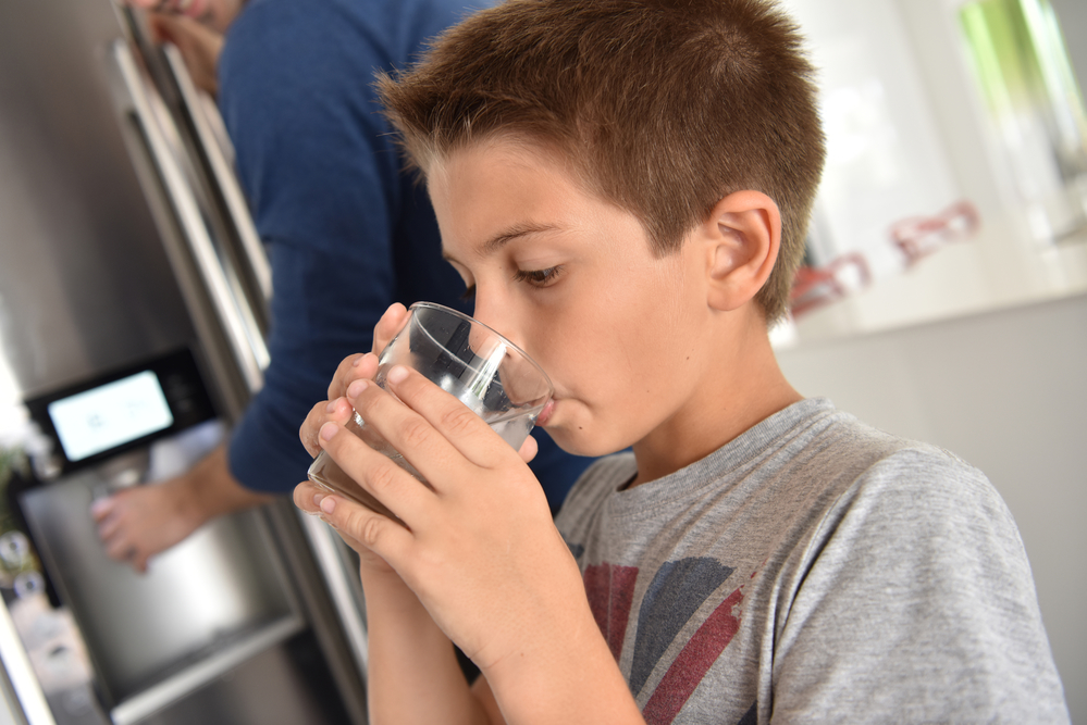 Young boy drinking fresh water